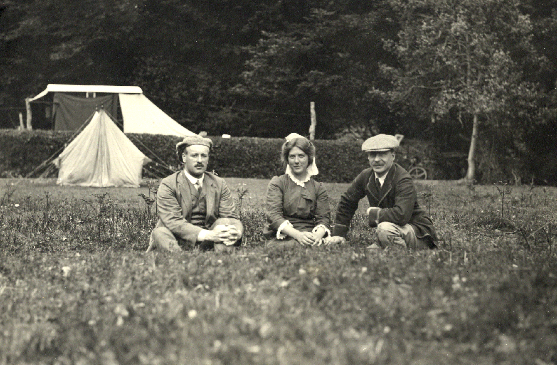 One lady and two men seated in a field in front of a caravan