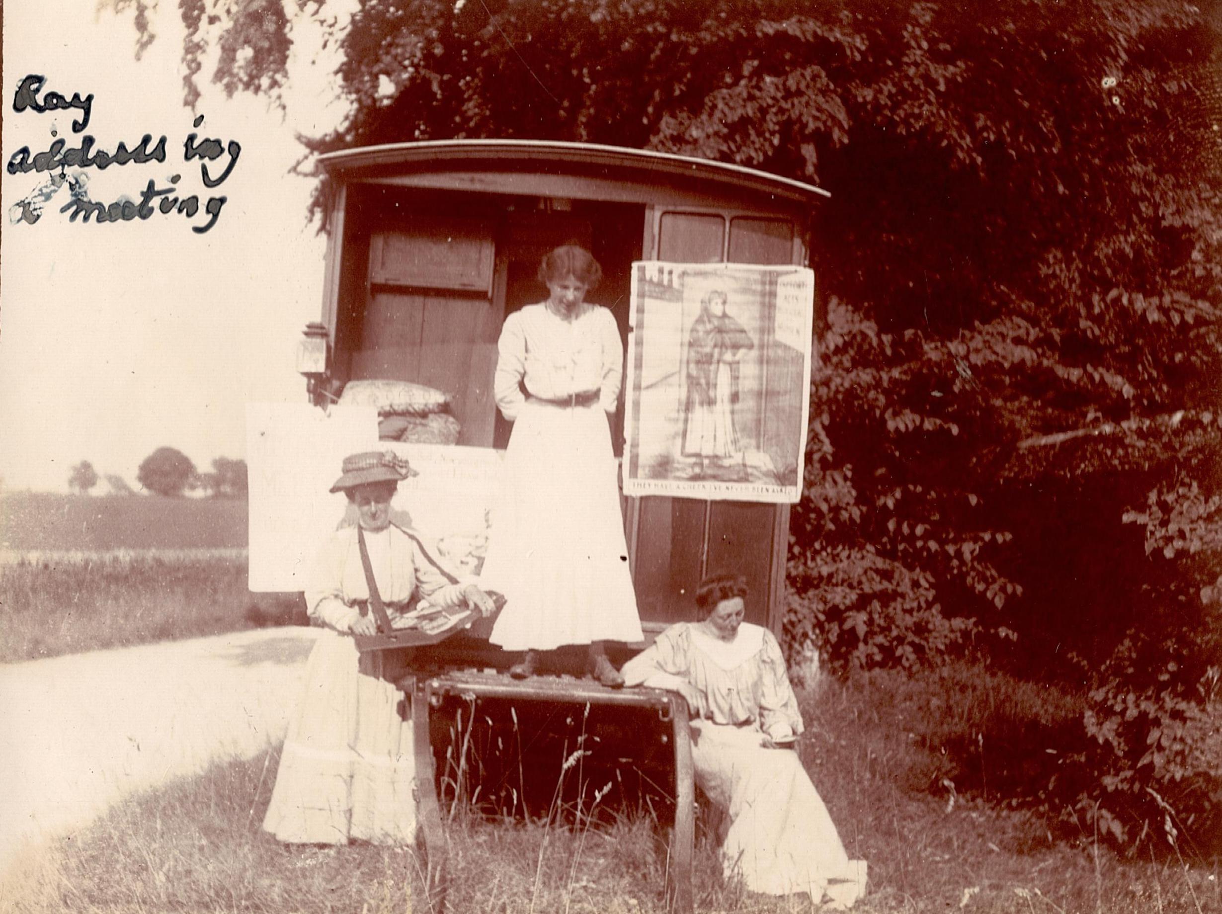 Women standing around a horse-drawn caravan