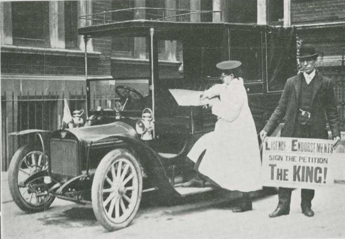 Image from the Car Illustrated of Vera 'Jack' Holme signing a petition next to a motor car