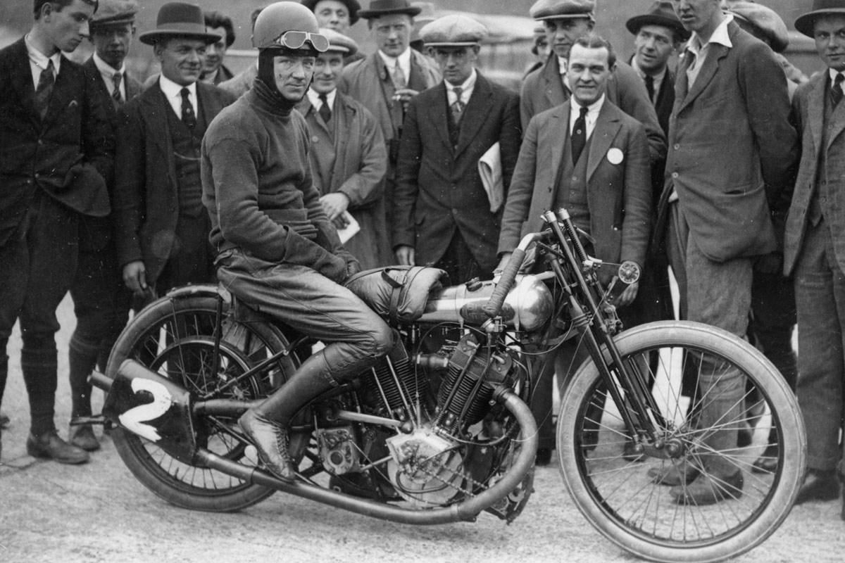 Bert Le Vack on motorcycle with group of men