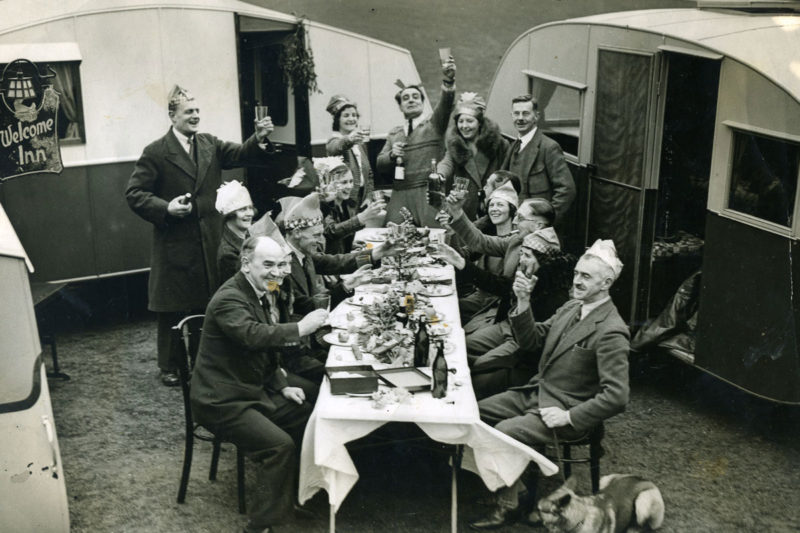 A group of people enjoying Christmas dinner on a table outside caravans.