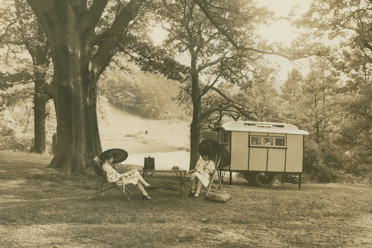 A caravan parked in a glade with two women relaxing