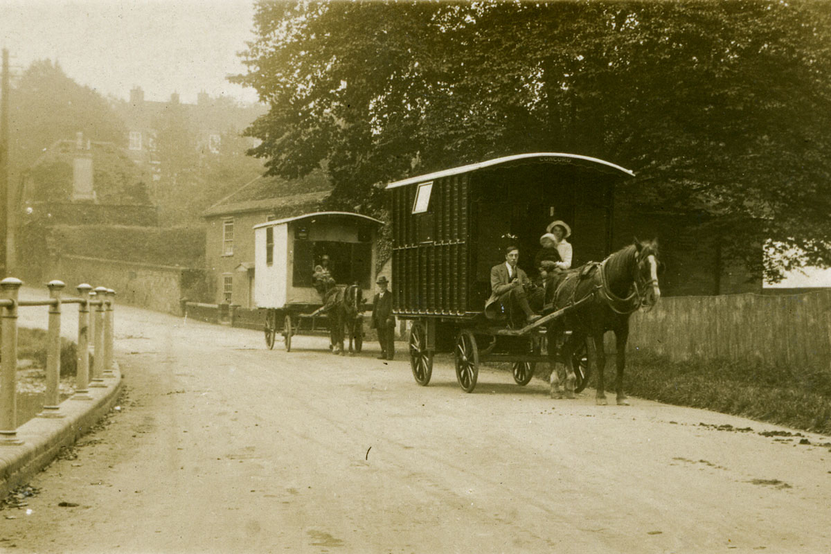 Two horse-drawn caravans travelling with families along a road