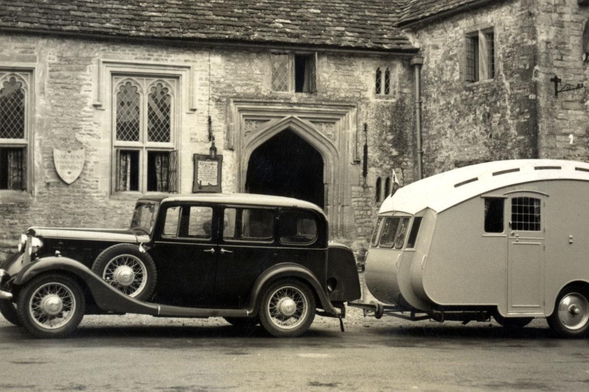 A car and caravan parked outside a stone built Inn.