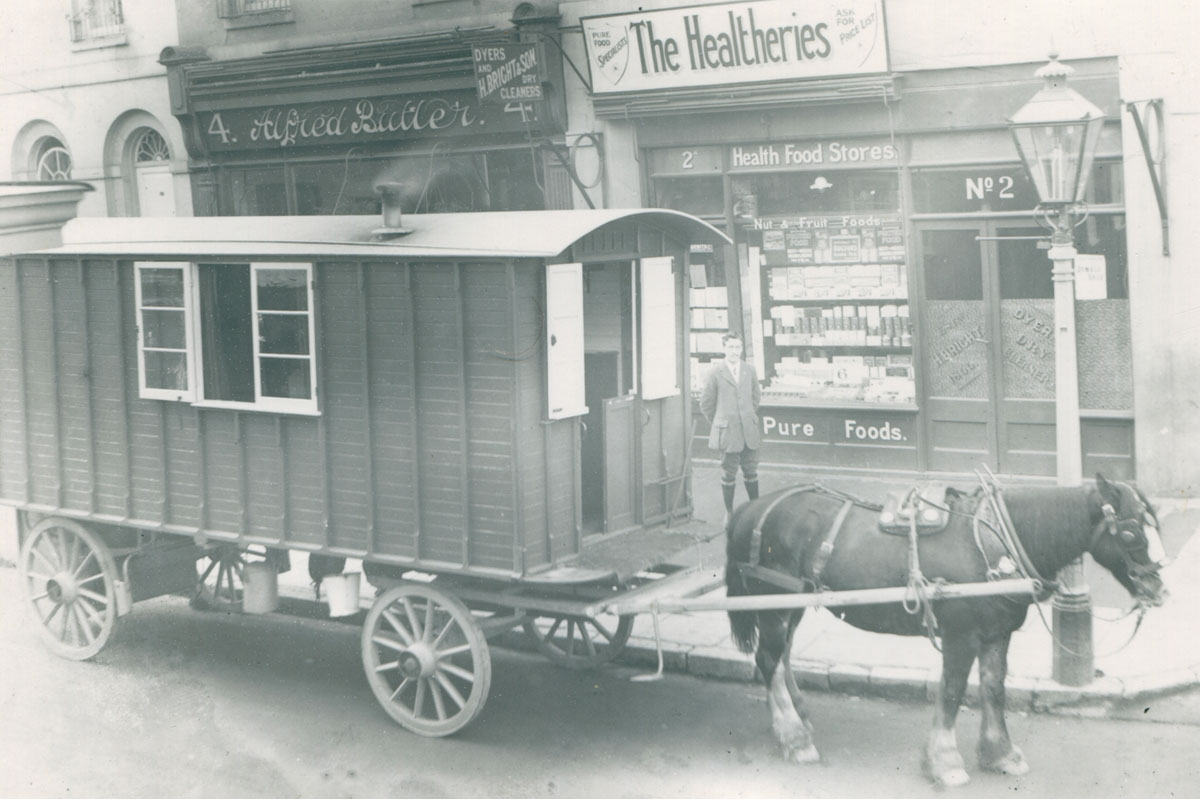 A horse drawn caravan and horse pictured parked outside a row of shops.
