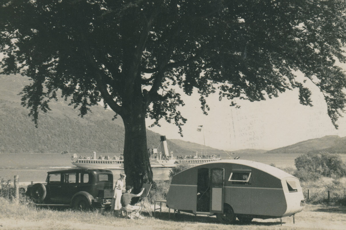 A car and caravan pictured in front of a loch with a paddle steamer in the background