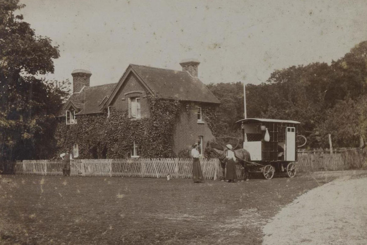 A horse drawn caravan parked outside a house