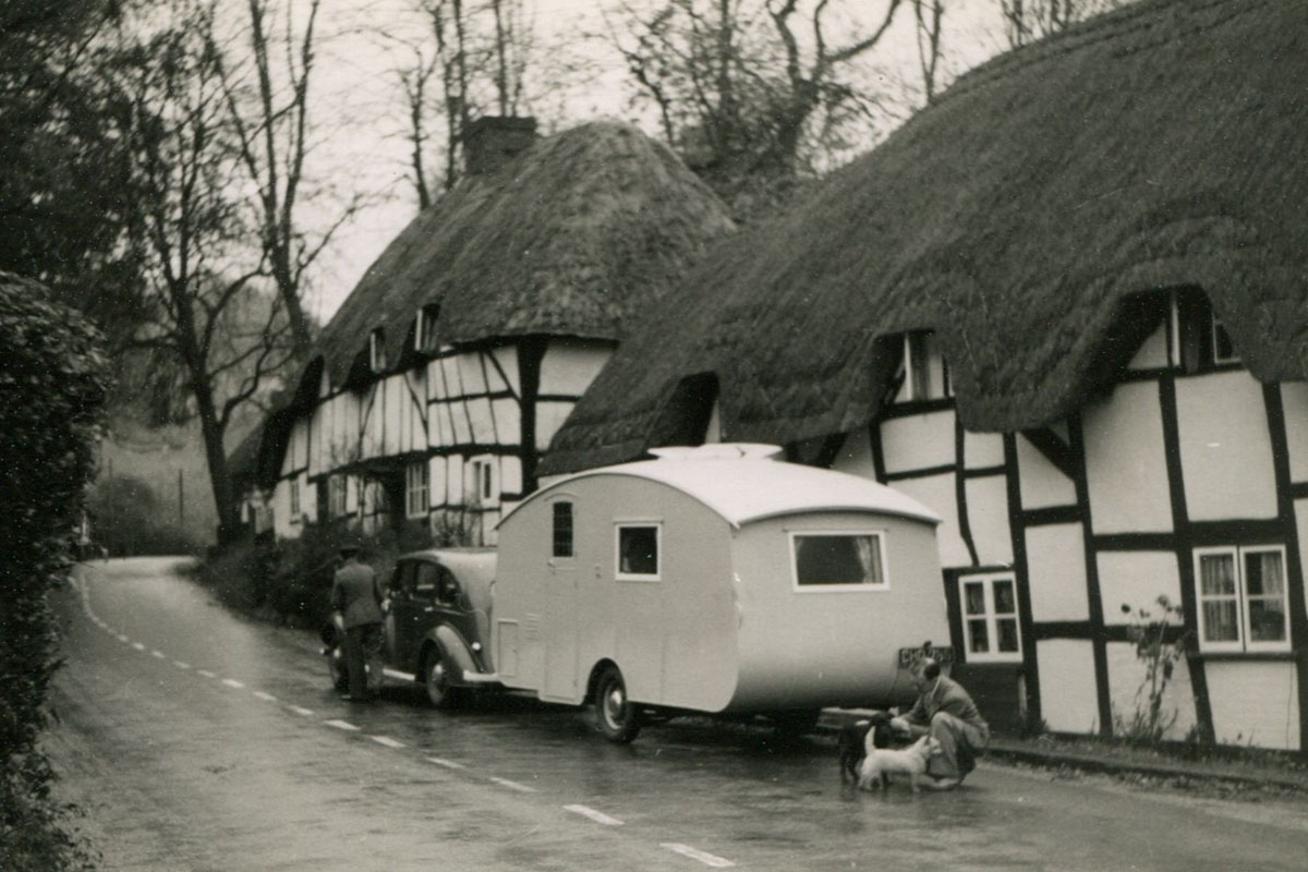 A car and caravan pictured outside a thatched cottage.
