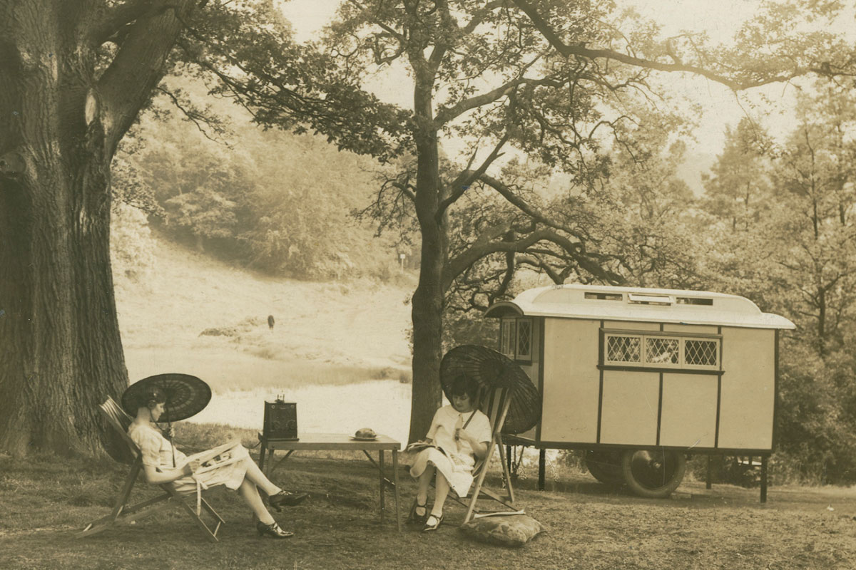 Two ladies with parasols in 1920s dress seated outside a trailer caravan in a woodland clearing