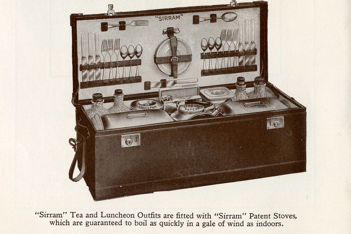 A dark box containing picnic accessories including cutlery, plates and flasks