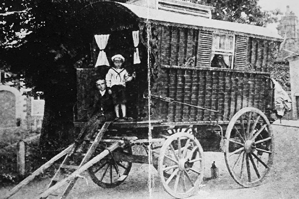 Two small boys standing at the front of a horse drawn caravan