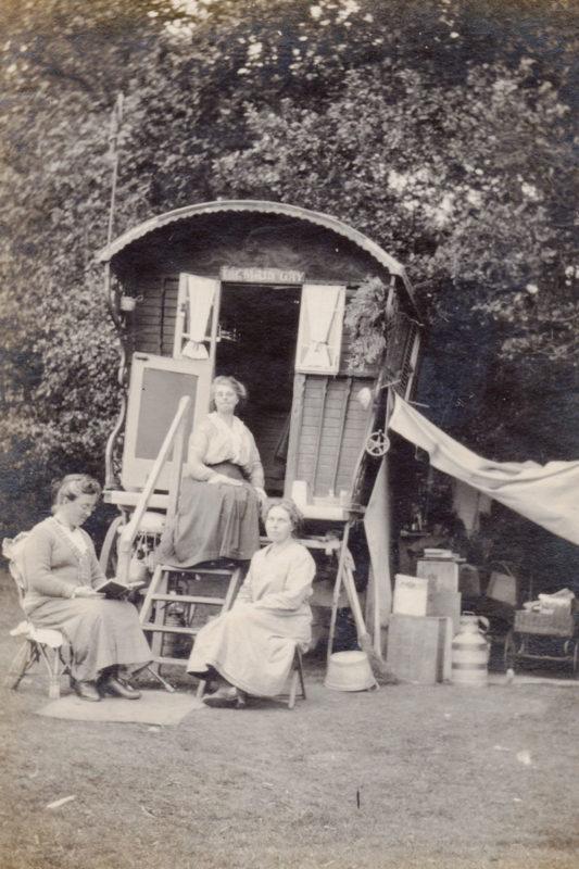 Three women seated outside a horse-drawn caravan