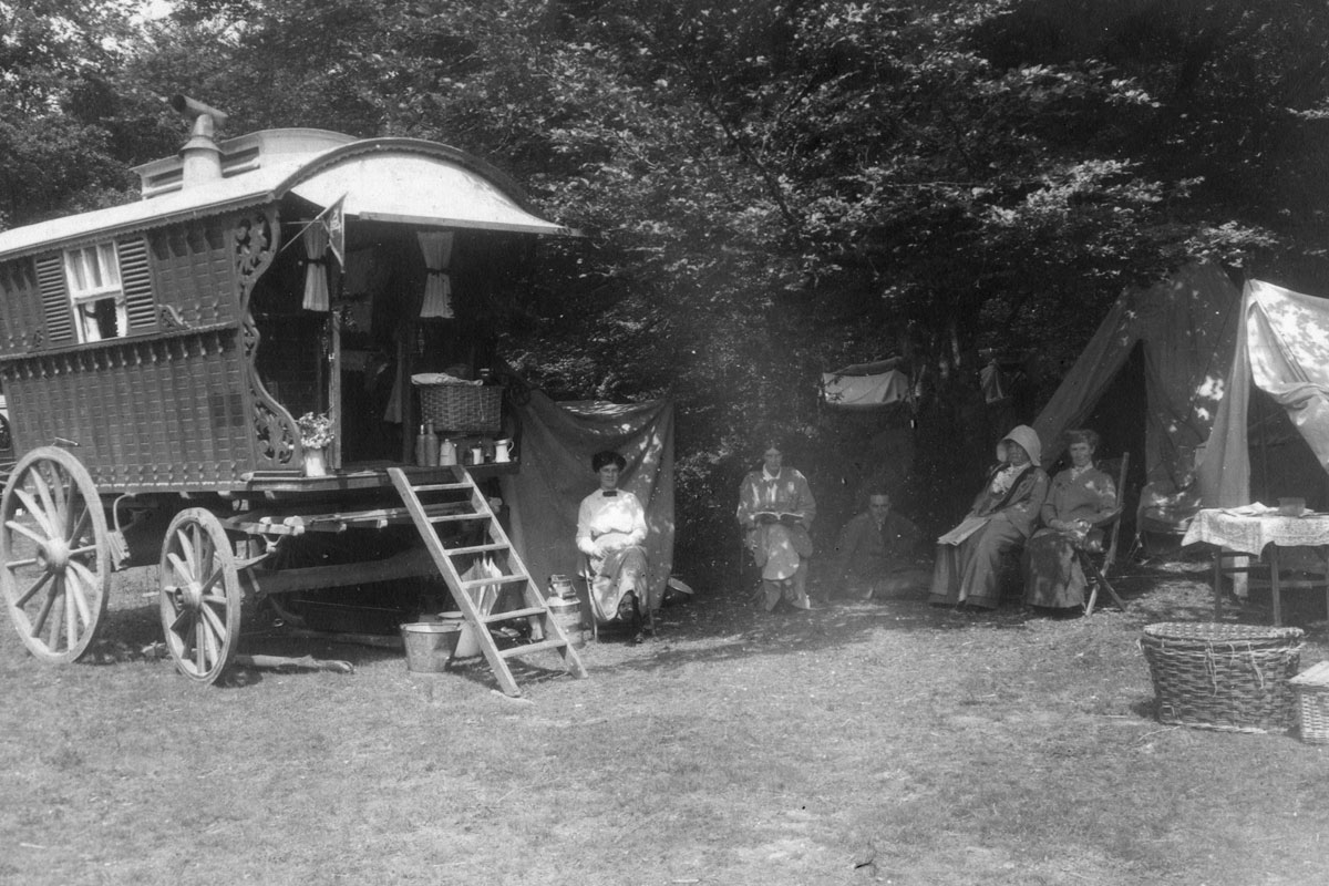 A horse drawn caravan pictured on the left with a group seated beside it
