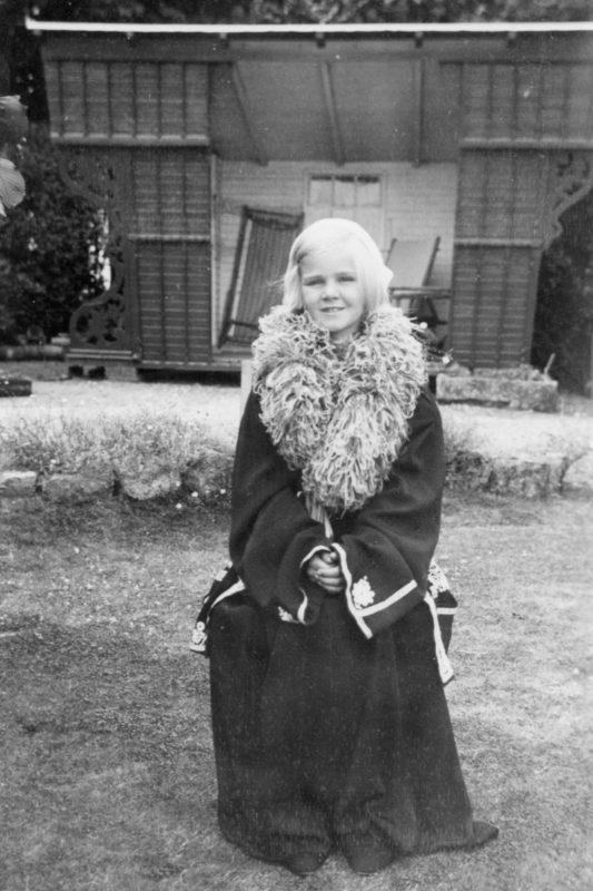 A girl in fancy dress standing in front of a shell of a caravan