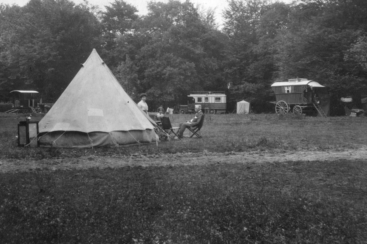 Caravans, a motorhome and a tent pitched in a clearing